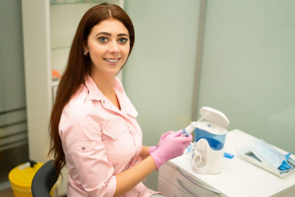 Dentystka demonstruje działanie irygatora. Czy wiesz, jak dbać o zęby nosząc aparat ortodontyczny?
