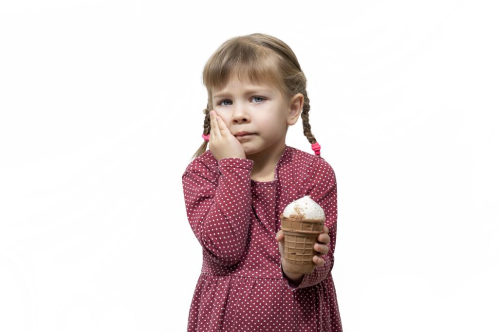 Dziewczynka z bolący zębem i lodem w dłoni. Nadwrażliwość zębów.