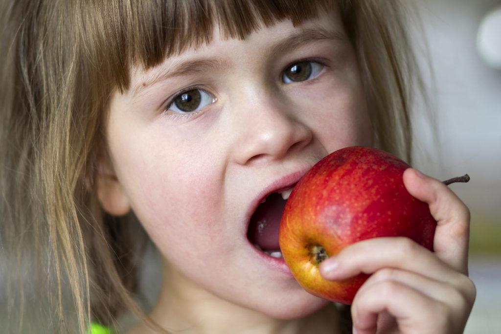 Dziewczynka je jabłko. Bezzębie - co może do niego doprowadzić i jakie są jego skutki